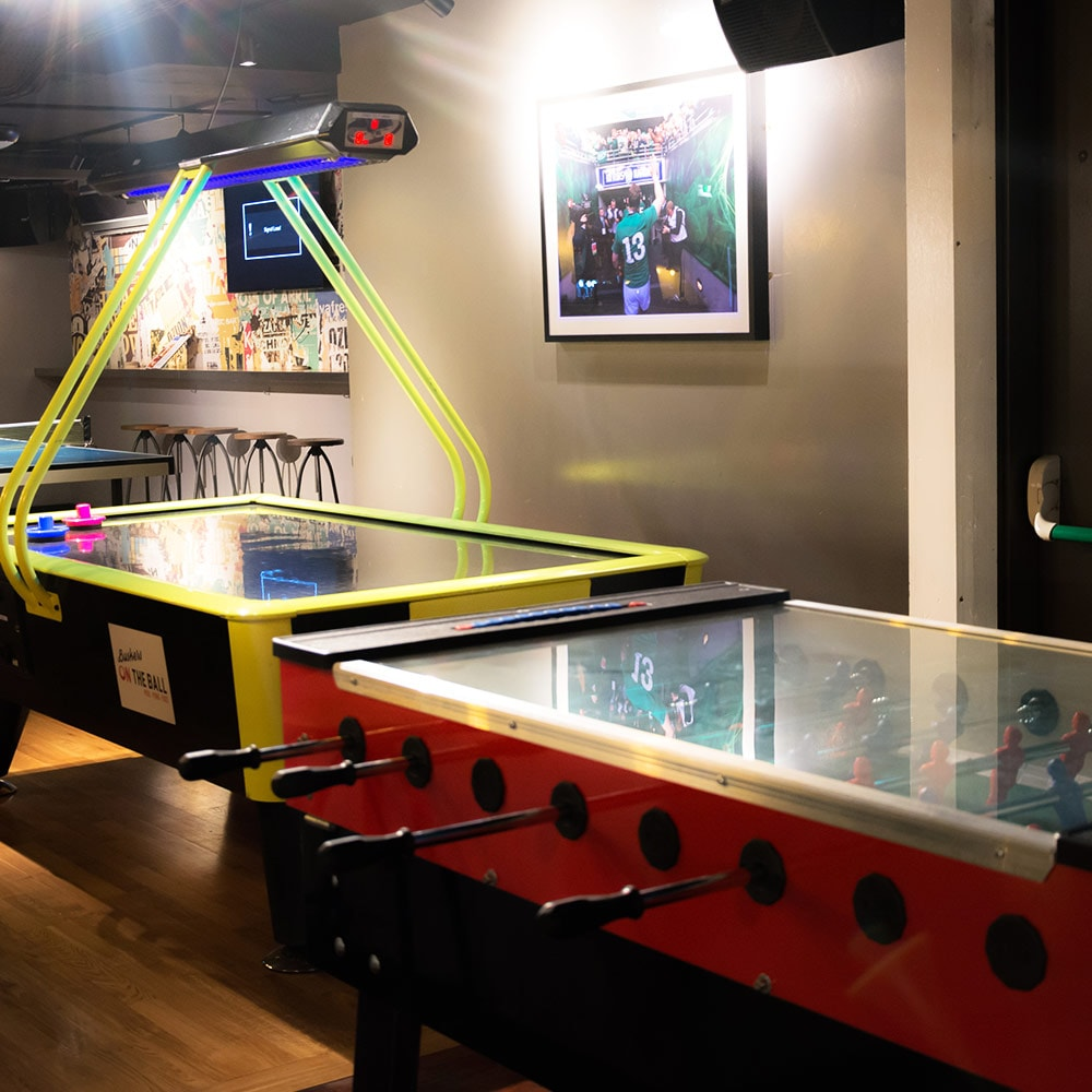 An air hockey table and a foosball table in a bar