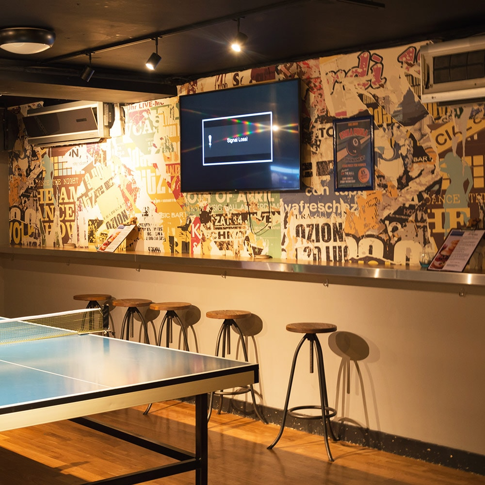 A TV on a wall with a ping pong table and bar stools in the foreground
