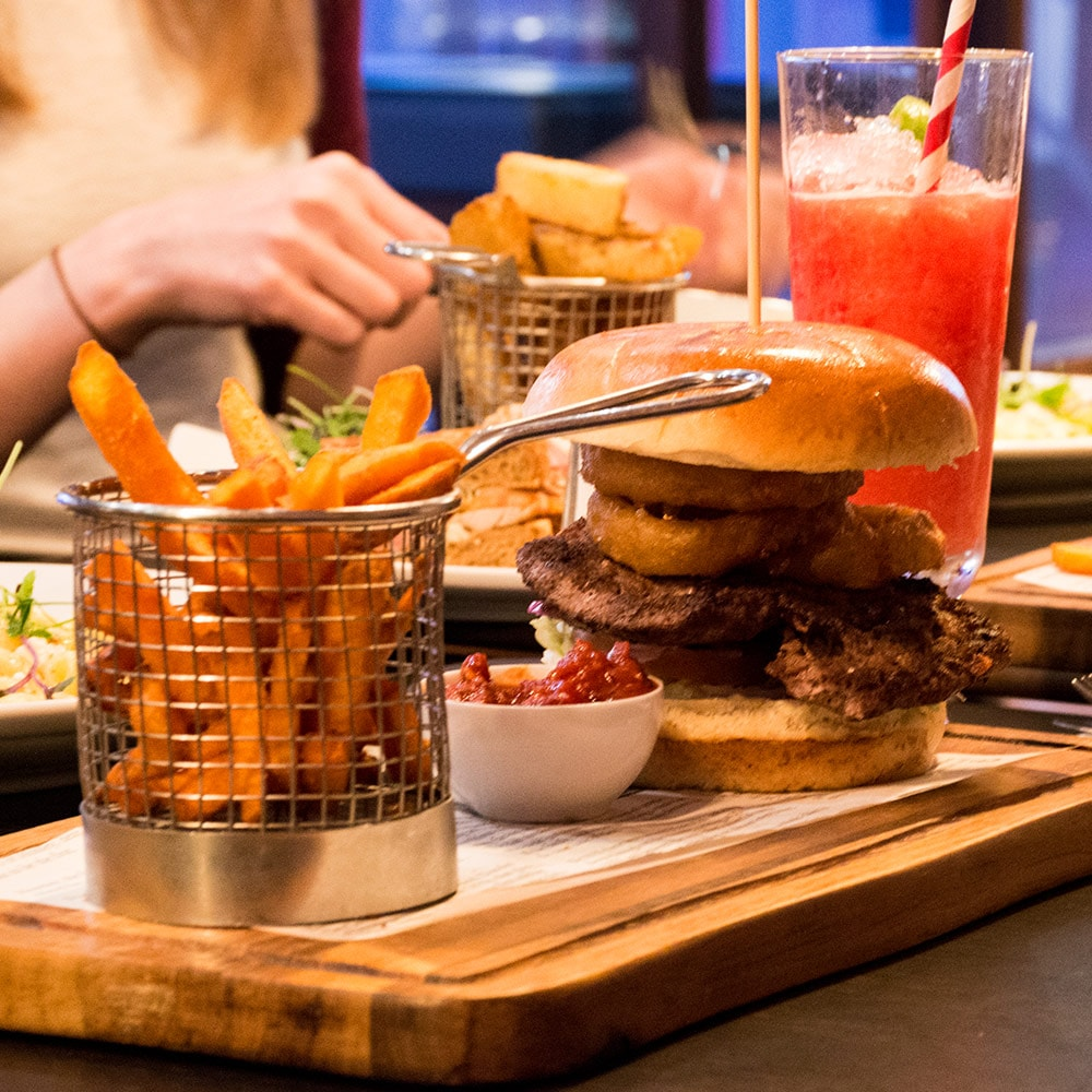 A burger served on a wooden board, with other dishes in the background