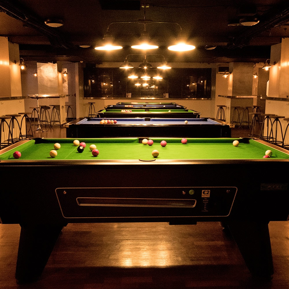 Five pool tables in one line, in a bar