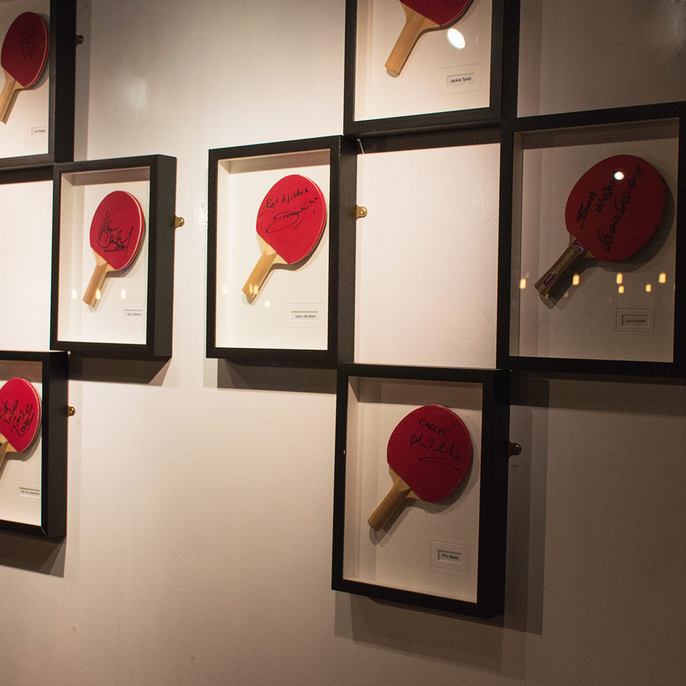 Framed ping pong bats hung up on a wall