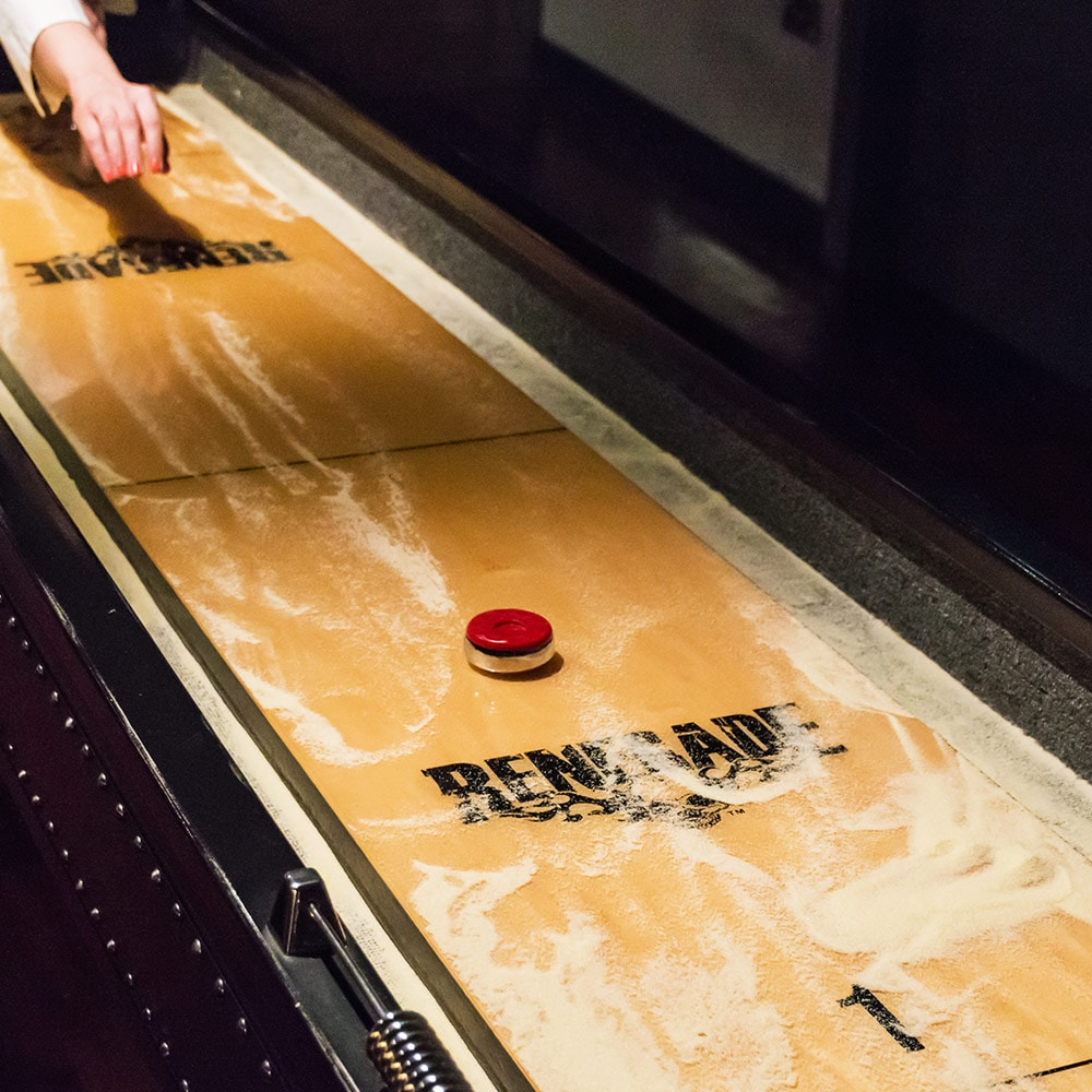 A woman's hand throwing a puck down a shuffle board table
