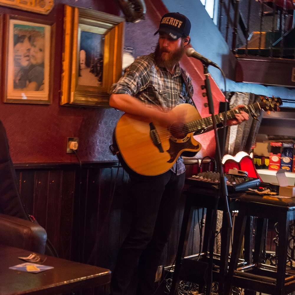 A man playing a guitar in a bar