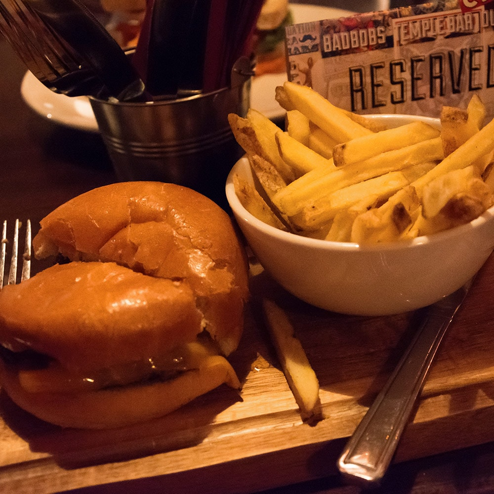 Close up of a burger and bowl of chips served on a wooden board