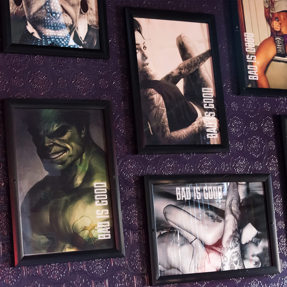 Framed pictures of quirky posters hung on a purple wall