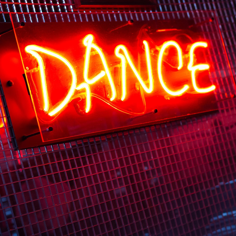 A lit up red Dance sign on a wall