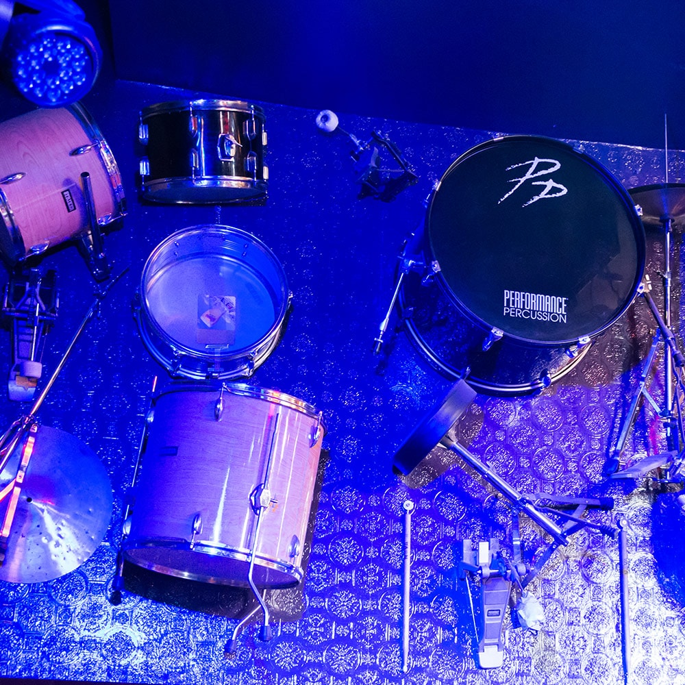 A drum kit hung up on a wall to a purple backdrop
