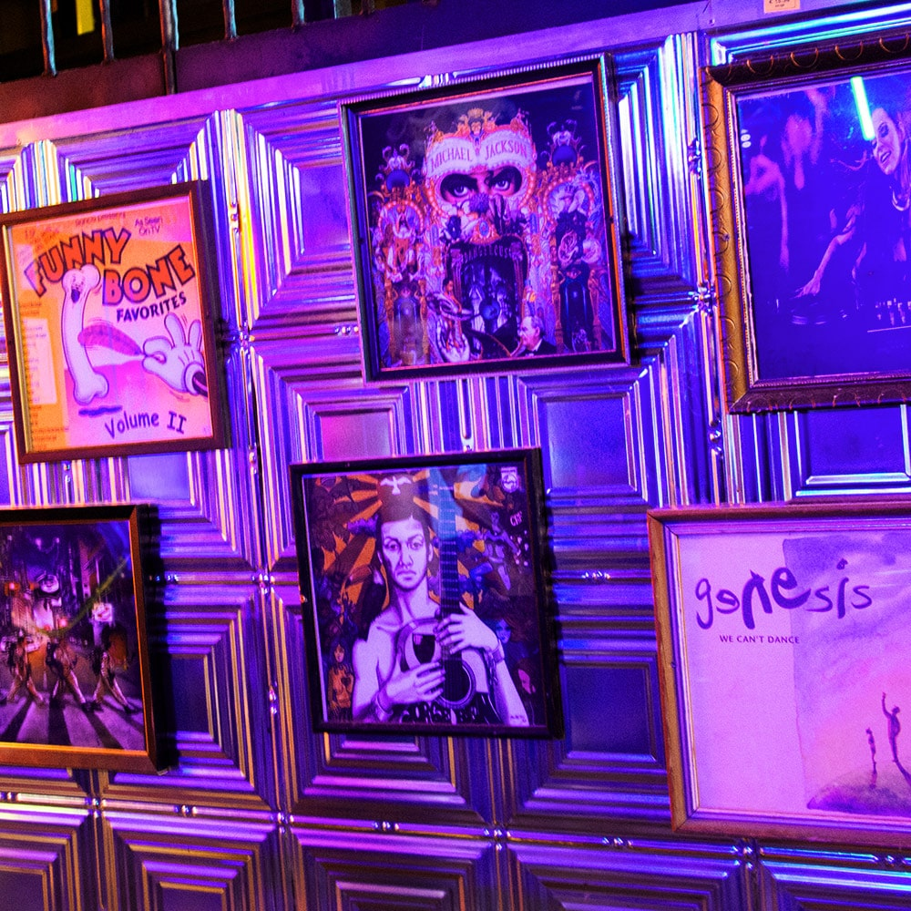 Framed pictures of quirky posters hung on a wall to a purple backdrop