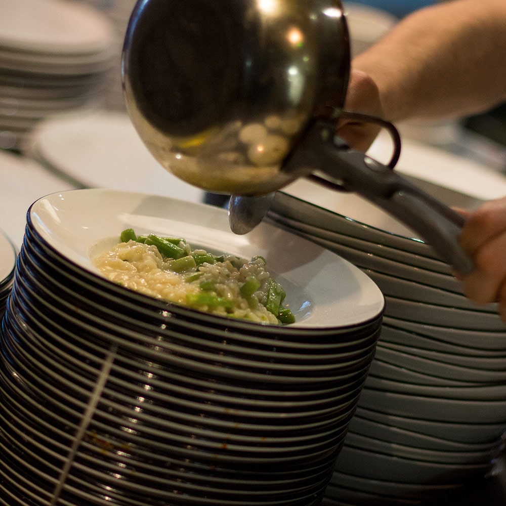 A chef pouring food onto a stack of plates from a pan