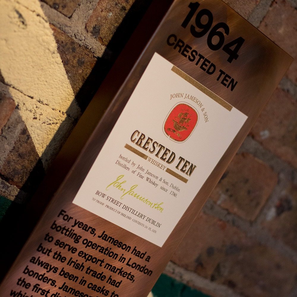 Close up of a sign detailing Jameson history on a brick wall