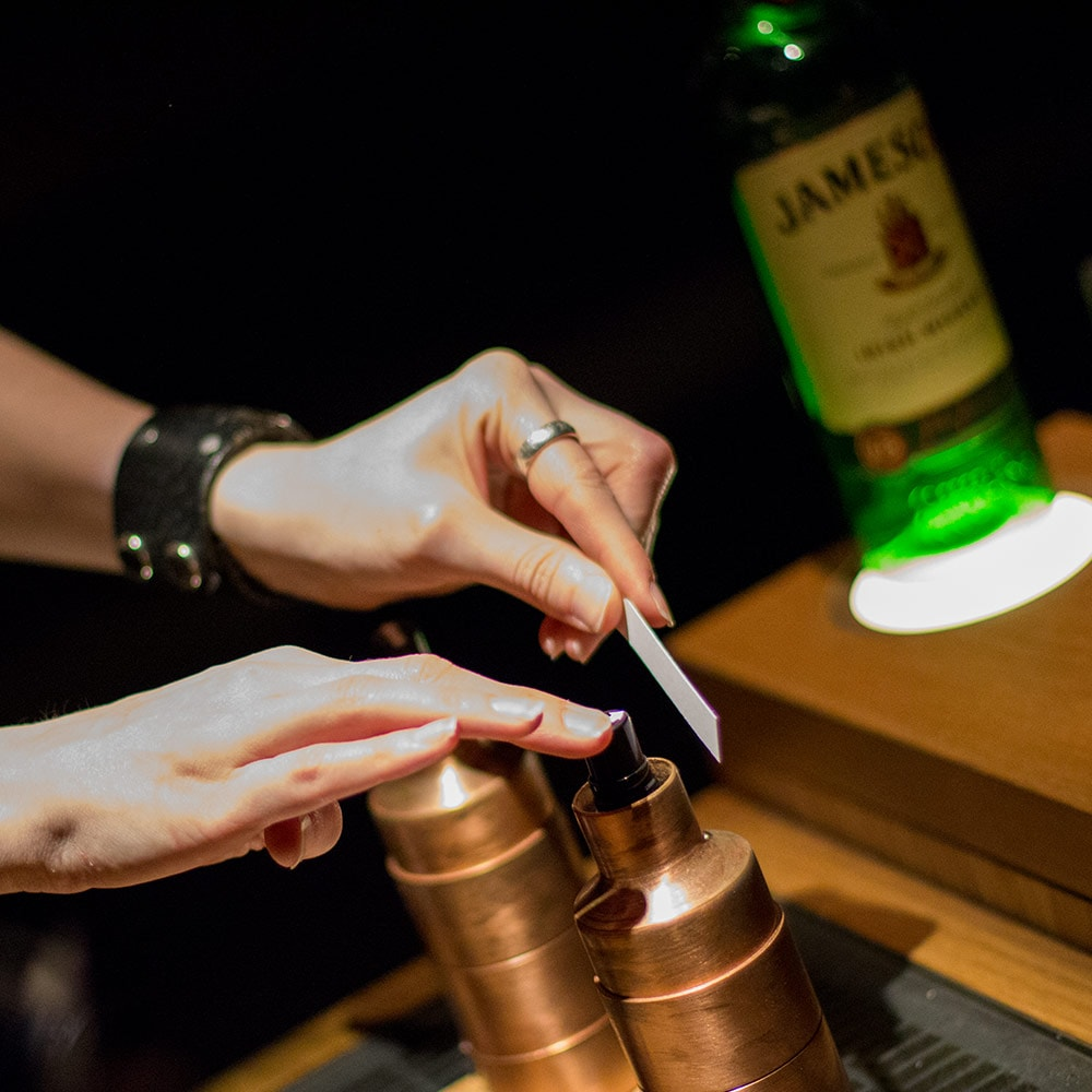 Close up of a hand spraying an atomiser onto a small piece of paper on the ingredients table at Jameson Whiskey distillery