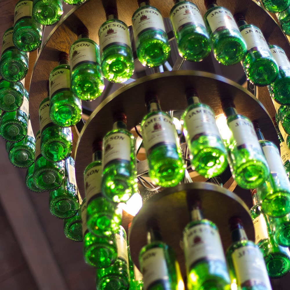 Jameson Whiskey bottles hung up in a chandelier