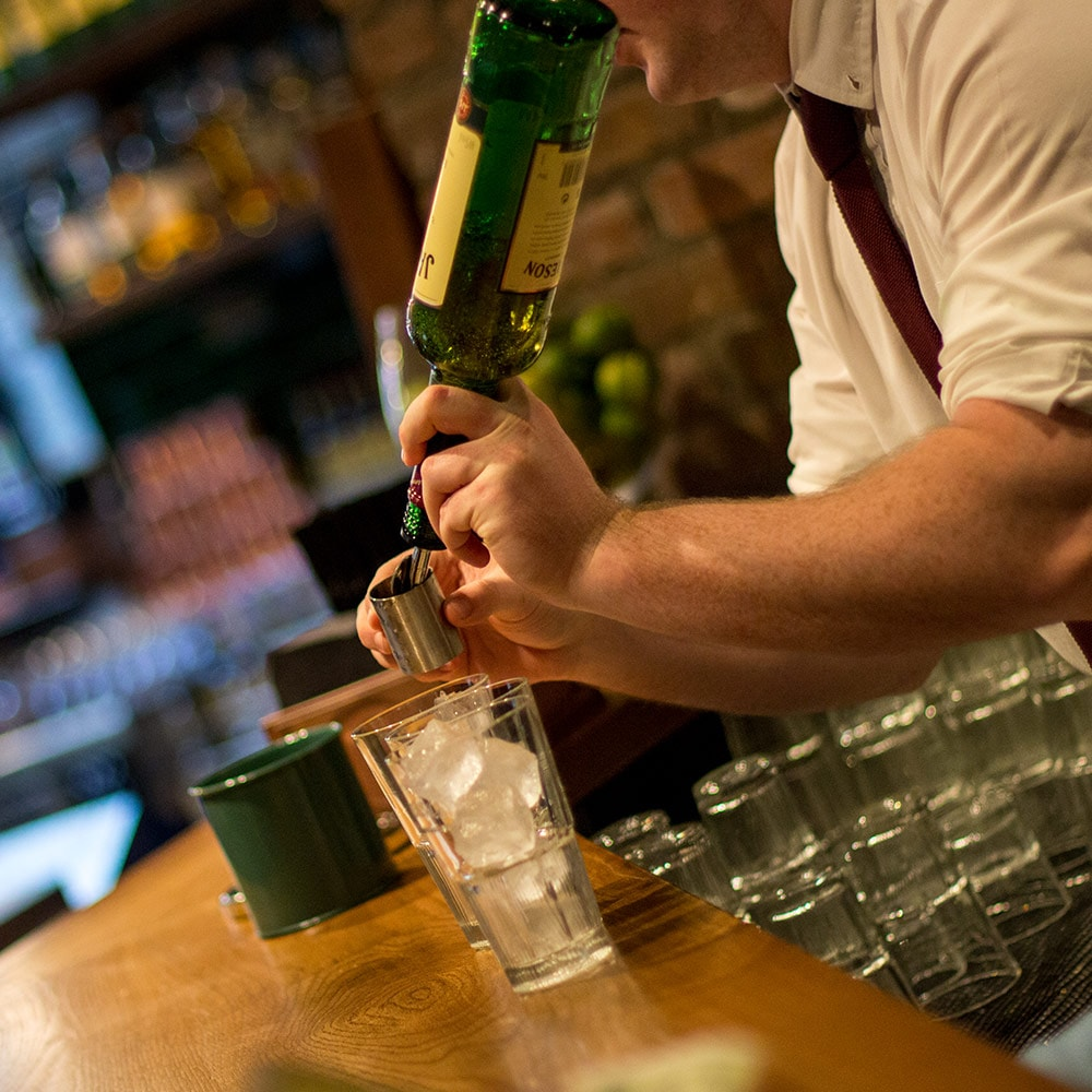 A man pouring a shot of Jameson Whiskey into a glass, over ice