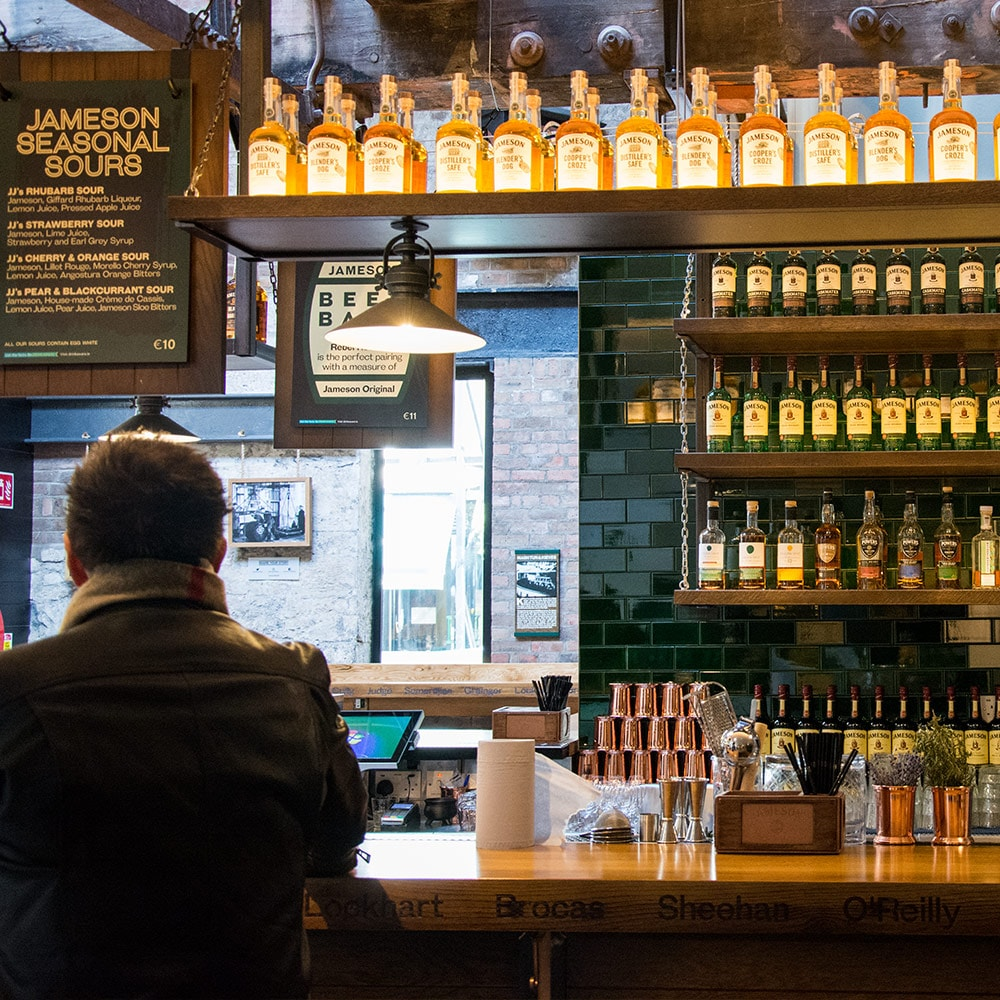 The bar at Jameson Whiskey distillery, with a woman sat at a stool