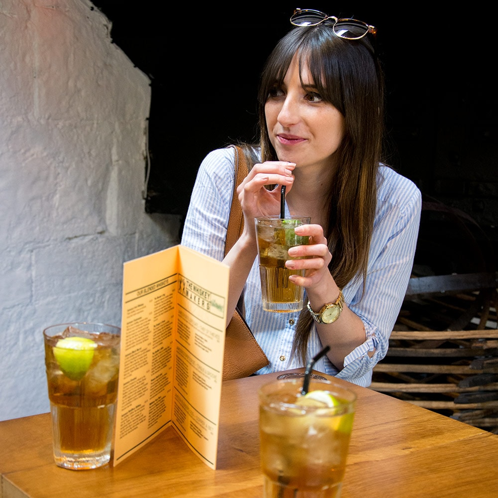 A woman drinking a glass of whiskey and ginger ale whilst sat at a table