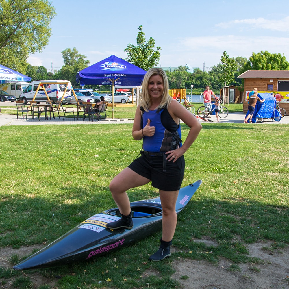 A woman holding her thumb up and posing with a kayak