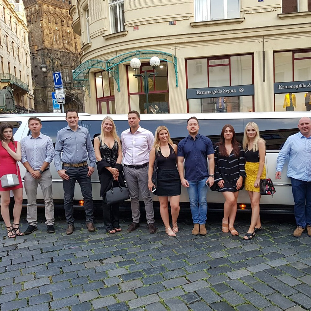 A group of people posing in front of a limo in the street