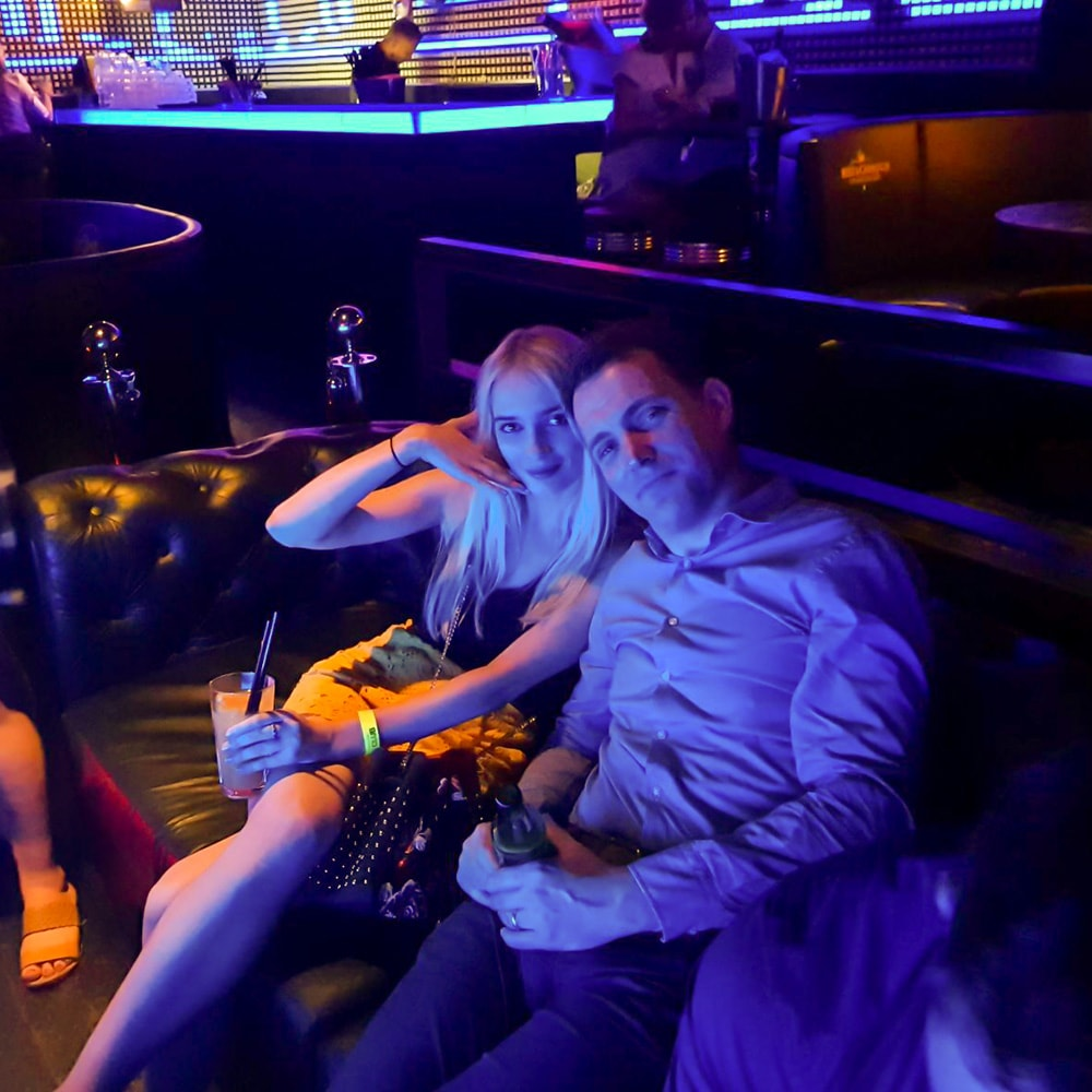 A man and woman sat together in a club