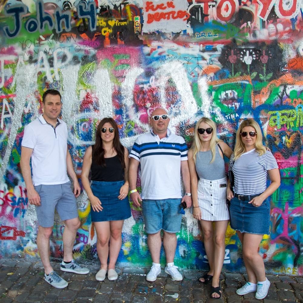Three men and two women stood in front of the John Lennon wall, Prague