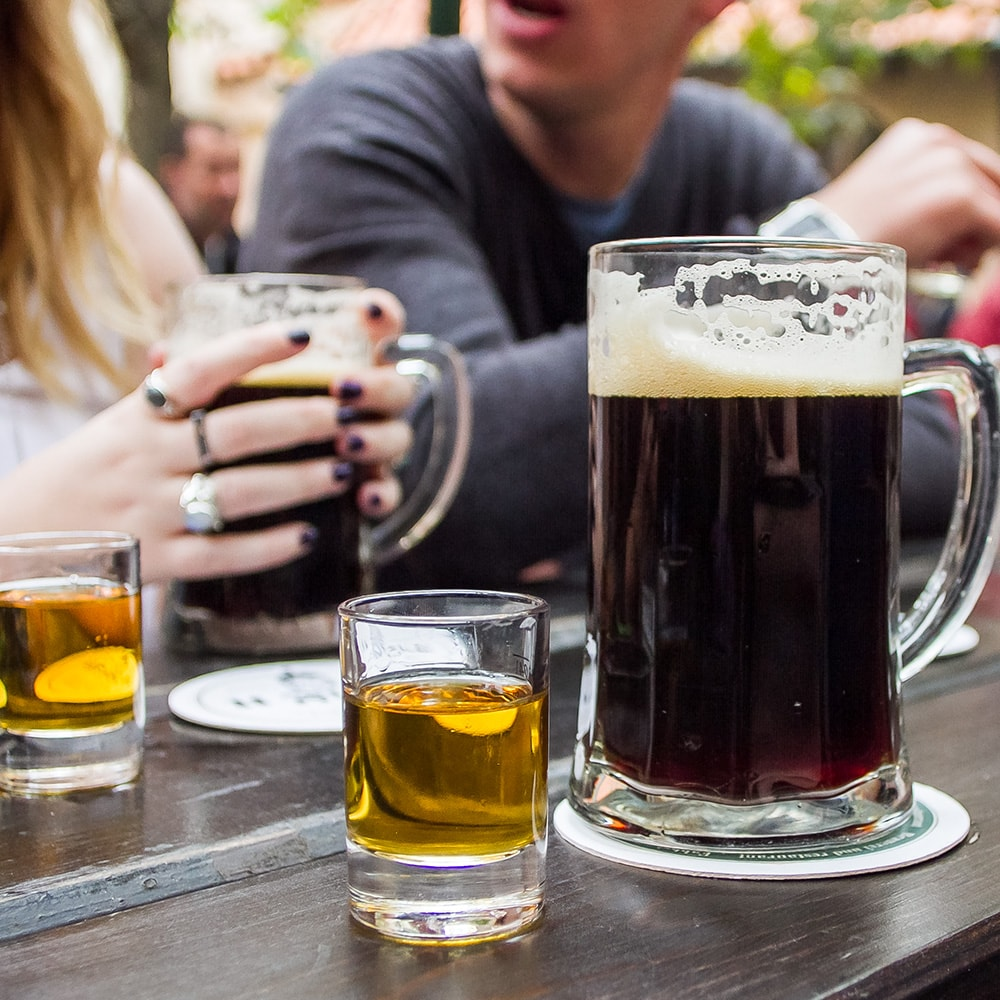 Tankards of beers and shots on a bench in the U Fleku beer garden