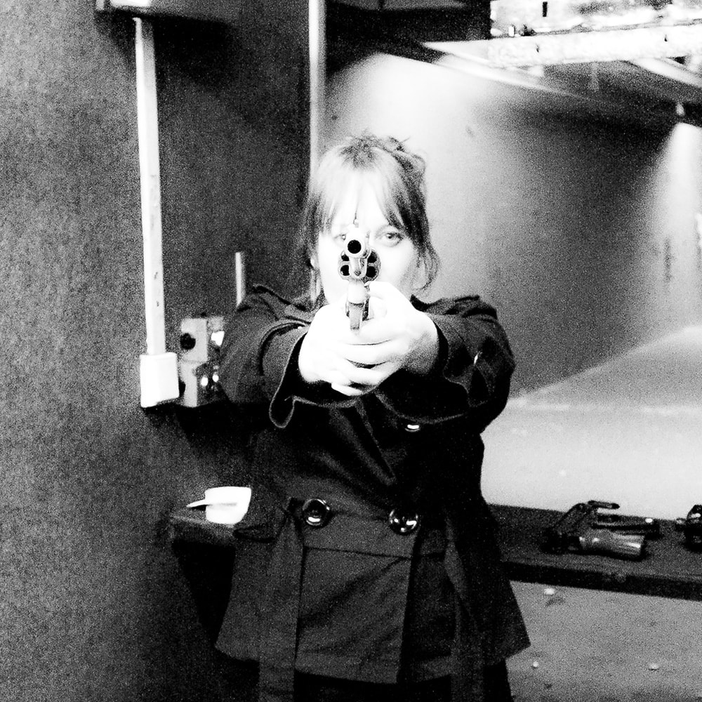 Black and white image of a woman pointing a gun at the camera