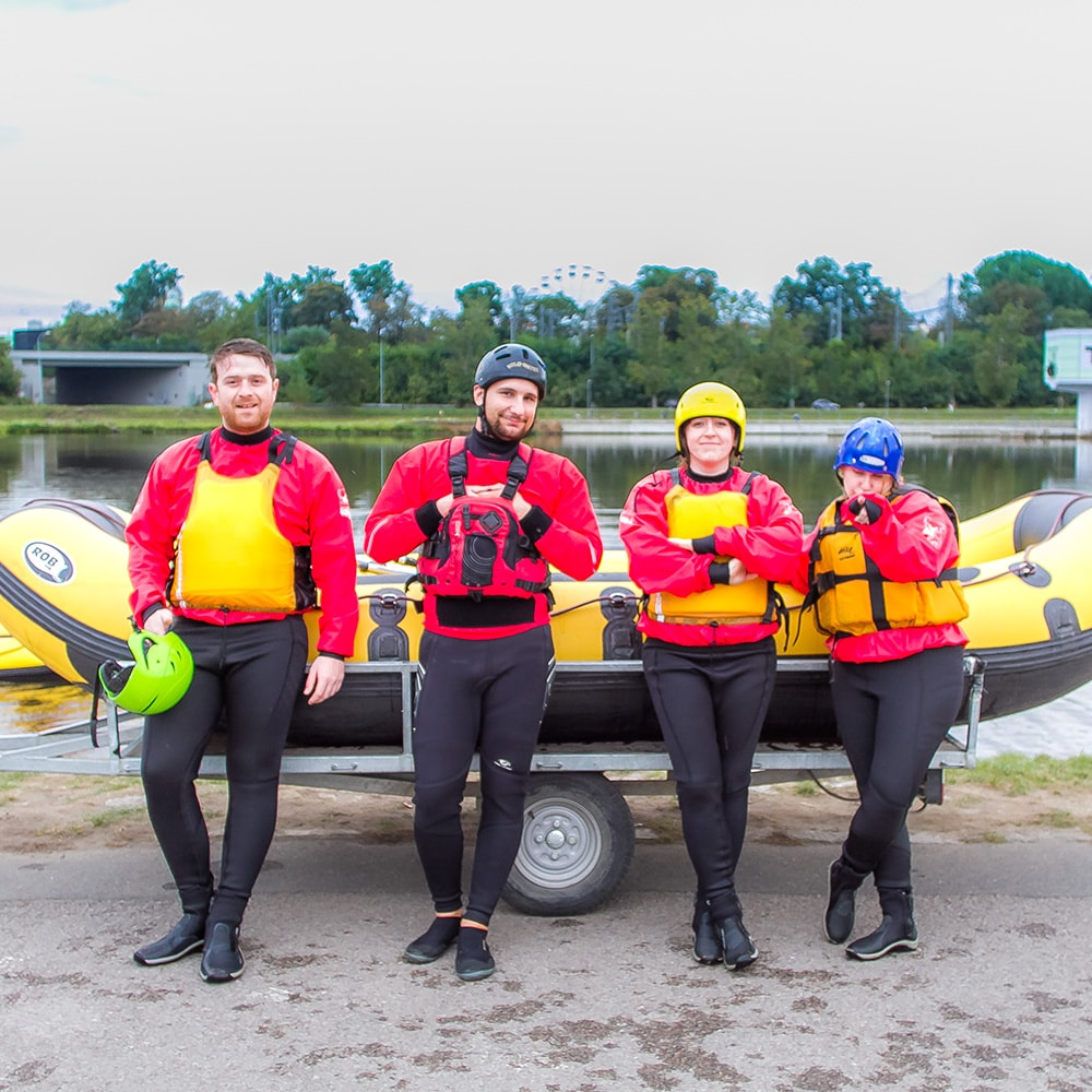 Four people standing in front of a raft in wetsuits and life jackets