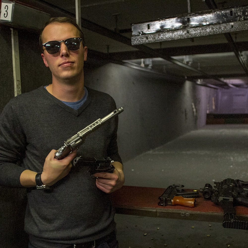A man holding two guns and posing for a photo at an indoor shooting range