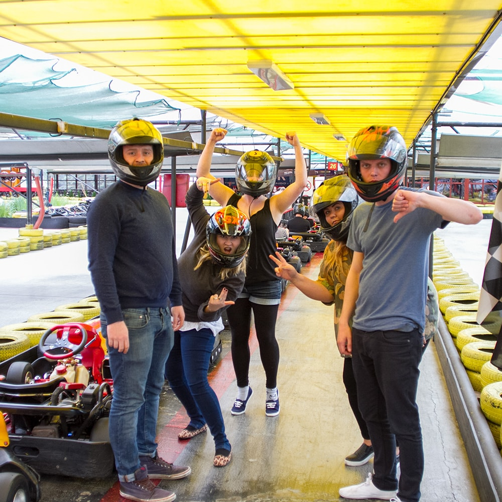 Men and women posing for a picture at Prague's indoor karting centre