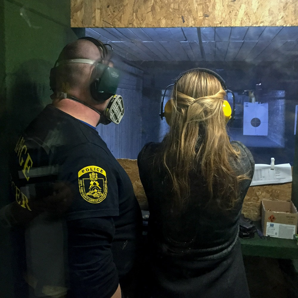 A girl being shown how to fire a gun by an instructor