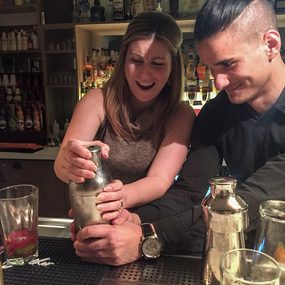 A woman being taught how to make a cocktail by a barman
