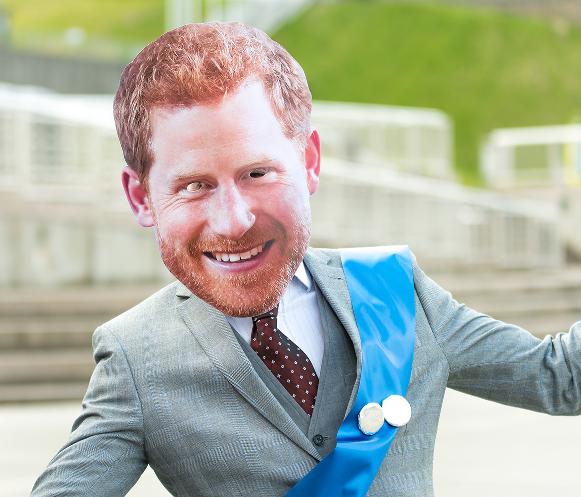 A man in a suit wearing a Prince Harry mask