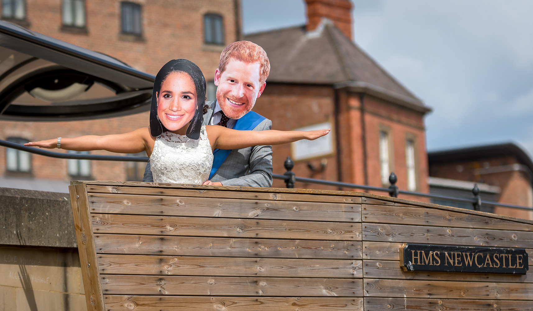 People wearing Prince Harry and Meghan Markle masks, posing like a scene from Titanic on HMS Newcastle