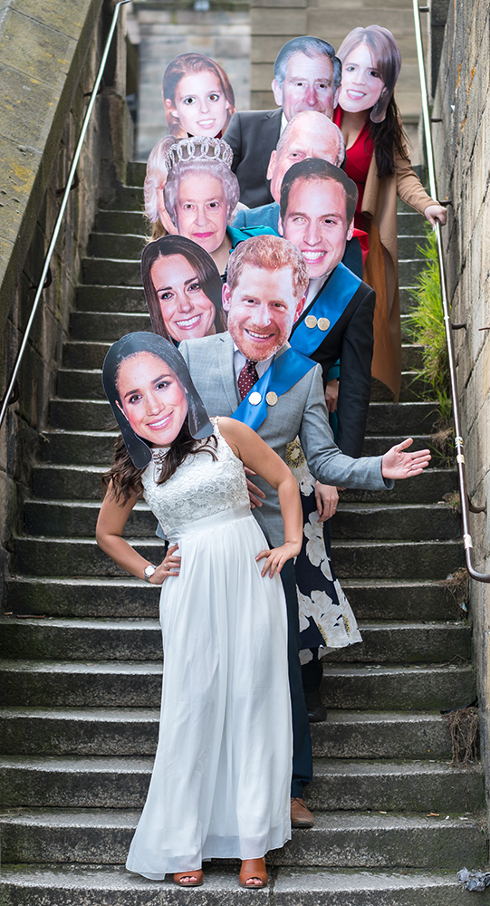 People wearing Royal Family masks posing on some stairs