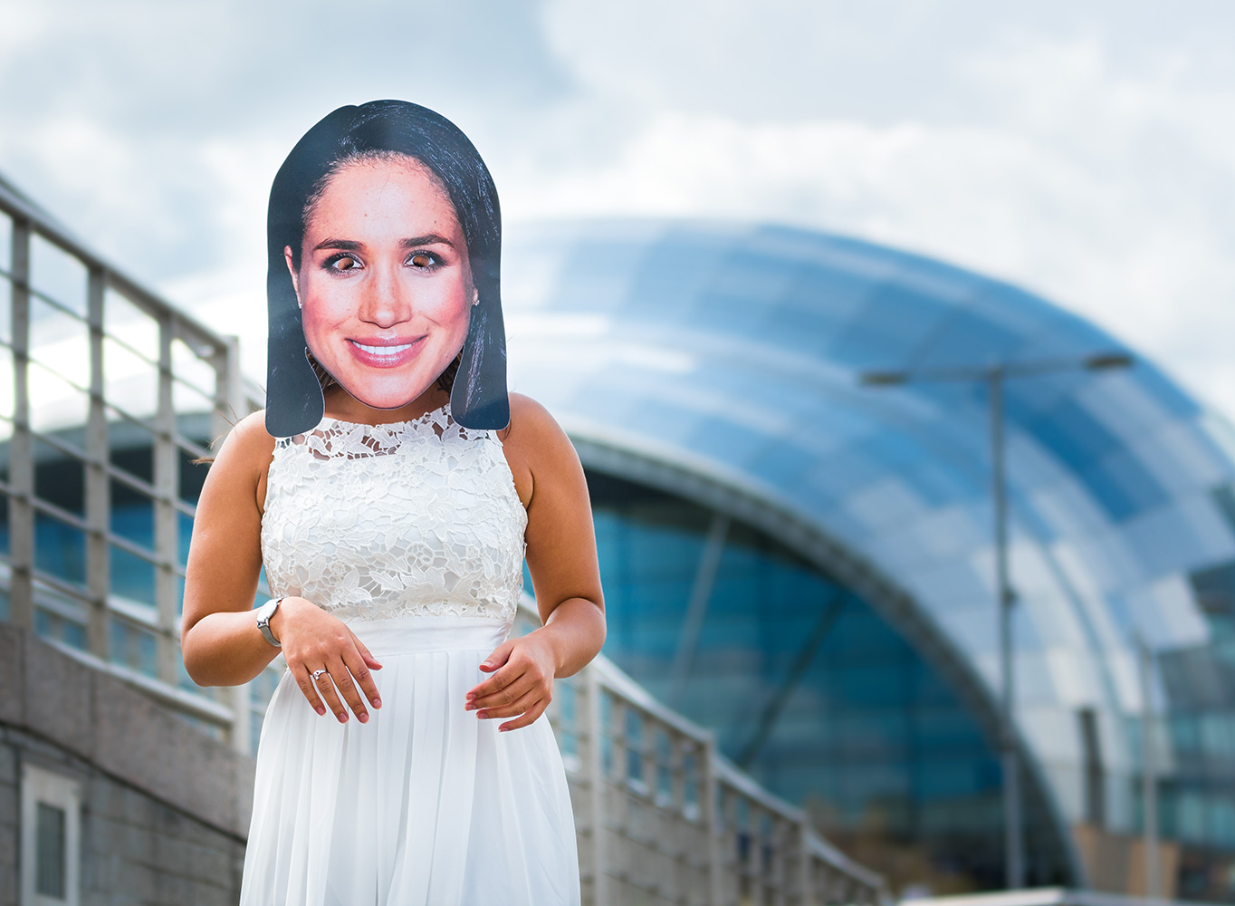 A girl in a wedding dress wearing a Meghan Markle mask, in front of The Sage in Newcastle
