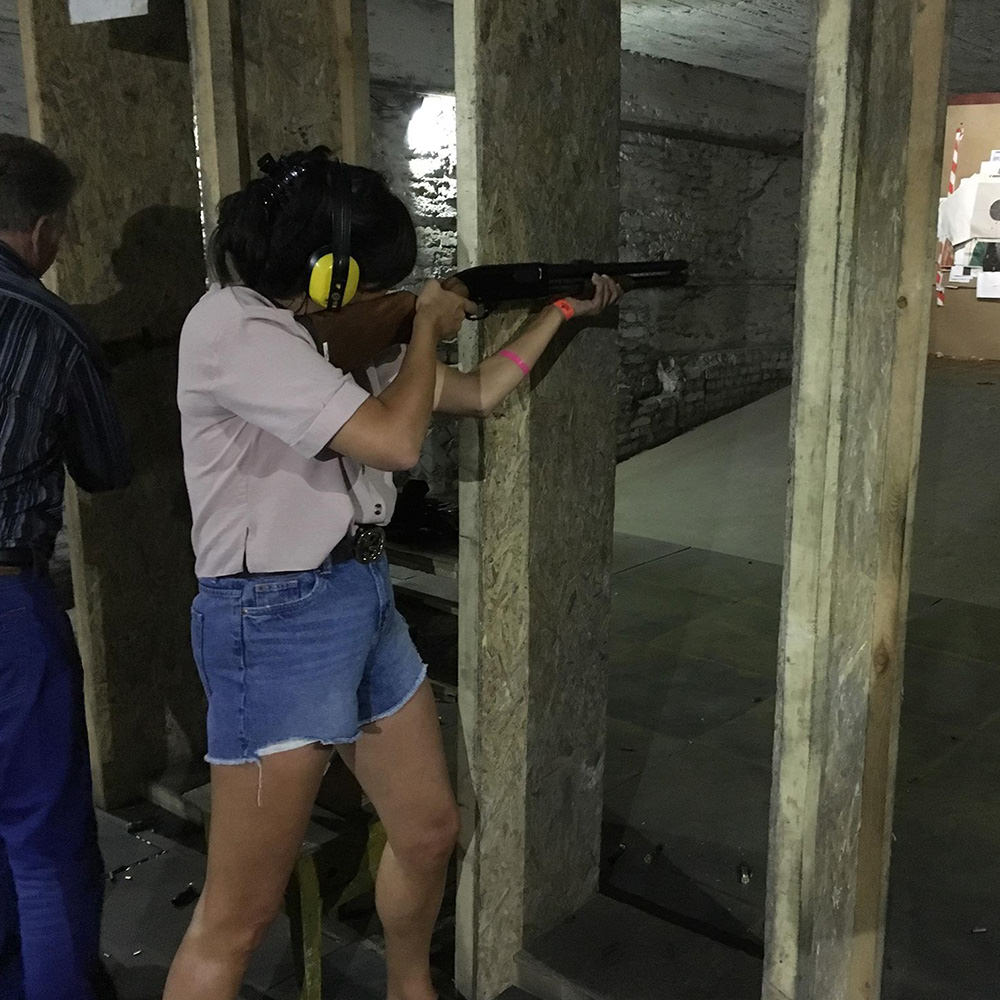 A girl firing a gun in a shooting range