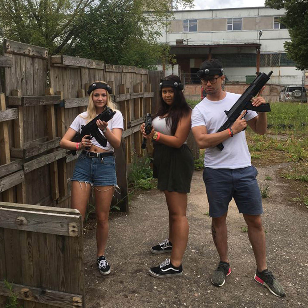 Three people holding laser guns outdoors