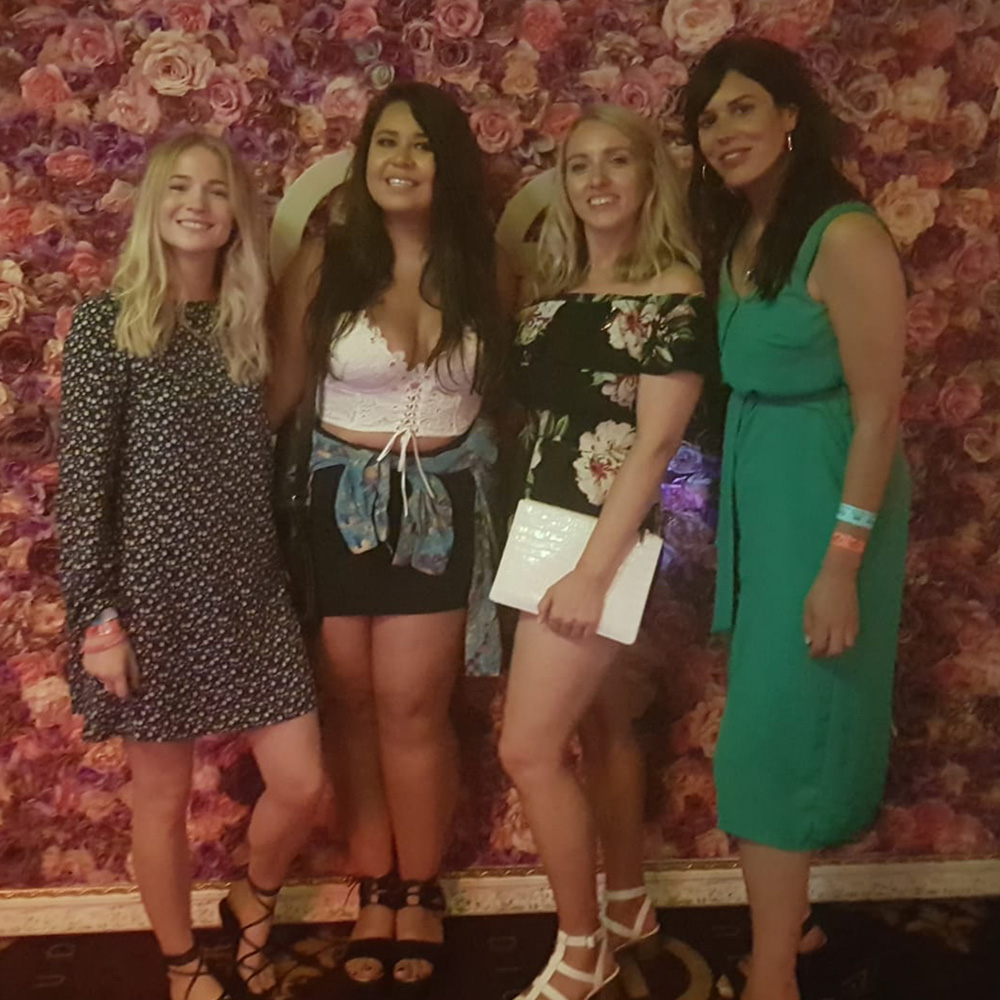 Some girls in front of a flower wall