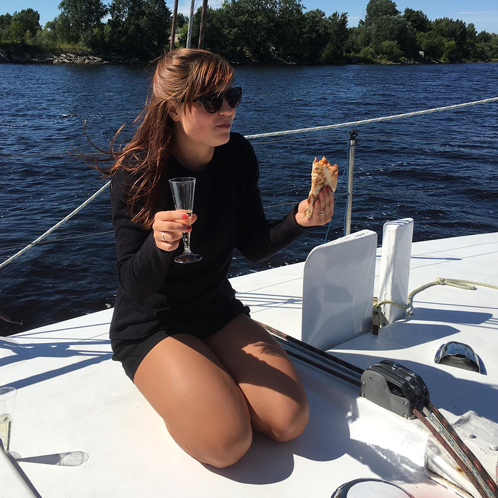 A girl eating pizza on board a yacht