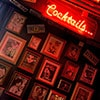 A lit up red cocktail sign on a wall, above framed pictures hung up