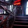 A winding staircase leading up to an upper level, with a red sign at the top of the stairs