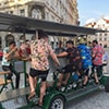 A group of men in Hawaiian-style shirts on a beer bike in Prague