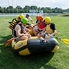 People sat in a raft on a patch of grass