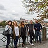 Five people posing for a picture in front of the river, in Prague