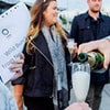 Close up of champagne being poured into a glass with people stood in the background