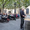 A bartender collecting glasses in a busy beer garden