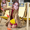 A girl wearing a Princess Eugenie mask, making a sandcastle at NE1's Quayside Seaside