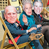 Three Last Night of Freedom members of staff wearing Royal Family desks, sitting on deck chairs at NE1 Quayside Quayside