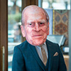 A man wearing a Prince Philip mask in Pitcher and Piano