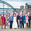 A group of people wearing Royal Family masks with the Tyne Bridge in the background