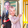 A girl wearing a Camilla mask holding a beach hut like a pole and a man wearing Prince Charles mask watching